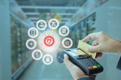 Kvinnlig kassörska som nallar kreditkorten med en handheld avläsare och symbol av betalningservice via kreditkort Arkivfoto