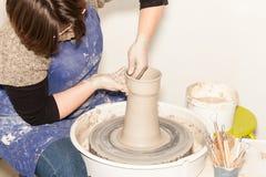Kvinnlig keramiker som skapar en jord- krus på keramikers hjul Royaltyfria Foton