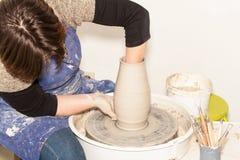 Kvinnlig keramiker som skapar en jord- krus på keramikers hjul Arkivbild
