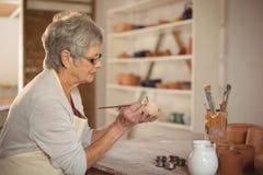 Kvinnlig keramikermålning på bunken royaltyfri bild