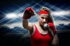 Kvinnlig kickboxer i boxning förbinder gör stansmaskin Royaltyfria Foton