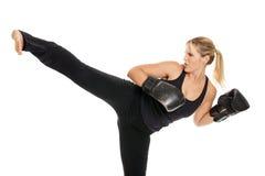 Kvinnlig kickboxer som gör en sida, sparkar Royaltyfri Bild