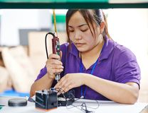 Kvinnlig kinesisk arbetare i fabrik Arkivbild