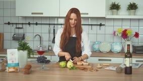Kvinnlig kock Cutting Fruit för ung kvinna på kök Rött huvudfolkslut upp arkivfilmer
