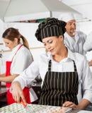 Kvinnlig kock Cutting Ravioli Pasta med kollegor arkivbild