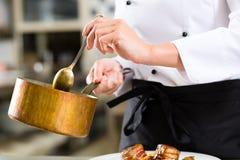 Kvinnlig kock i restaurangkökmatlagning Arkivbild