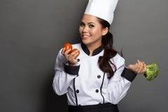 Kvinnlig kock som är klar att laga mat Fotografering för Bildbyråer