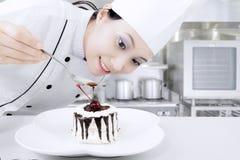 Kvinnlig kock som förbereder den söta kakan Arkivbild