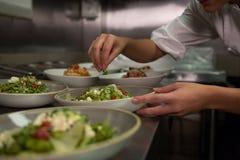 Kvinnlig kock som garnerar aptitretareplattor på beställningsstationen Royaltyfri Foto