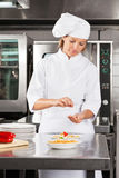 Kvinnlig kockGarnishing Dish At räknare Royaltyfria Foton