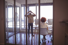 Kvinnlig kollega med affärsmannen som i regeringsställning bär VR-hörlurar med mikrofon royaltyfria bilder