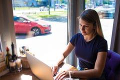 Kvinnlig kompetent annonsör som skriver befordrings- text på webbplats via netbook royaltyfria bilder