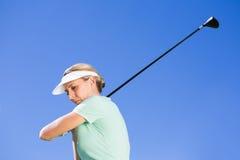 Kvinnlig koncentrera golfare som tar ett skott Royaltyfri Fotografi