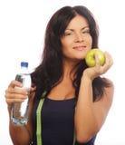 Kvinnlig konditionmodell som rymmer en vattenflaska och ett gräsplanäpple Arkivfoto