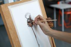 Kvinnlig konstnär i hennes rymliga vita studio som arbetar med vattenfärgmålning arkivfoto