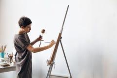 Kvinnlig konstnär i hennes rymliga vita studio som arbetar med vattenfärgmålning fotografering för bildbyråer