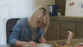 Kvinnlig konstnär som drar en bild på hennes skrivbord stock video
