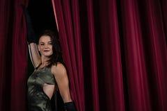 Kvinnlig konstnär som framme poserar av den massiva röda etappgardinen Fotografering för Bildbyråer
