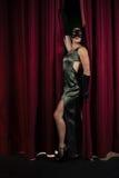 Kvinnlig konstnär som framme poserar av den massiva röda etappgardinen Arkivfoto