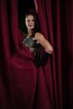 Kvinnlig konstnär som framme poserar av den massiva röda etappgardinen Royaltyfri Foto