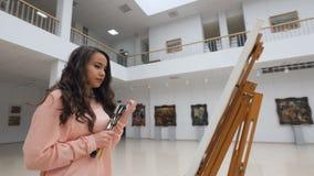 Kvinnlig konstnär som framme står av tom kanfas arkivfilmer