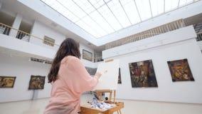 Kvinnlig konstnär som målar en bild i konstgalleri arkivfilmer