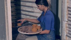 Kvinnlig konstnär som sätter clayware in i krukmakeribrännugnen lager videofilmer