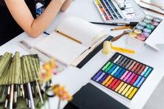 Kvinnlig konstnär som skapar bilden på arbetsplatsen genom att använda gouache, vattenfärgmålarfärger uppsättning och målarpensel royaltyfri bild