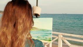 Kvinnlig konstnär som utomhus målar en seascape arkivfilmer