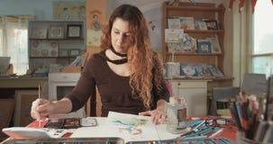 Kvinnlig konstnärmålning i hennes studio arkivfilmer