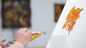 Kvinnlig konstnärstart som målar en bild på kanfas Konstgalleribakgrund 4K lager videofilmer