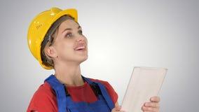 Kvinnlig konstruktionstekniker med en minnestavladator på en konstruktionsplats på lutningbakgrund royaltyfri foto