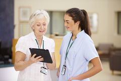 Kvinnlig konsulentIn Meeting With sjuksköterska Using Digital Tablet royaltyfri fotografi