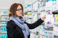 Kvinnlig konsument som väljer produkten i apotek Fotografering för Bildbyråer