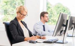 Kvinnlig kontorsarbetare i formalwear med hennes kollega arkivfoton