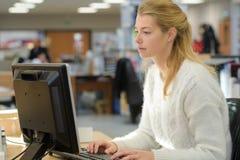 Kvinnlig kontorsarbetare med datoren royaltyfri bild