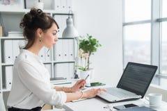 Kvinnlig kontorsarbetare som använder bärbara datorn på hennes arbetsplats och att bläddra information som surfar internet, ståen royaltyfri bild