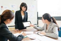 Kvinnlig kontorsarbetare som använder den mobila digitala minnestavlan royaltyfria foton