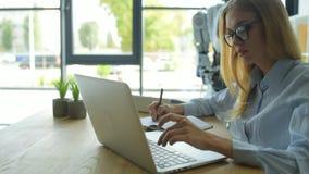 Kvinnlig kontorsarbetare som talar till roboten, medan skriva arkivfilmer