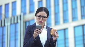 Kvinnlig kontorschef som äter den sjukliga hamburgaren som kontrollerar meddelanden på telefonen, spänning royaltyfri foto