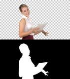 Kvinnlig kontorskontorist som går med minnestavlan och i huvudsak ler, när tala till kameran, Alpha Channel royaltyfri fotografi