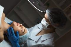 Kvinnlig kosmetologdoktor med patienten i wellnessmitt E royaltyfri bild