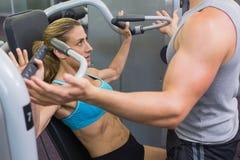 Kvinnlig kroppsbyggare för personlig instruktörcoachning som använder viktmaskinen Arkivbilder
