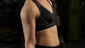 Kvinnlig kroppsbyggare som hårt arbetar för att bygga muskler som förbereder sig för konkurrens arkivfilmer