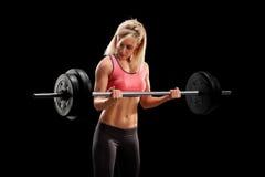 Kvinnlig kroppsbyggare som lyfter en tungvikt Arkivfoto