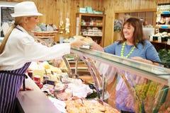 Kvinnlig kund för försäljningsassistentportion i matvaruaffär Royaltyfria Bilder