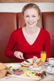 Kvinnlig kund som applicerar smör på bröd arkivfoton