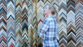 Kvinnlig kund som söker efter en ram i atelier Arkivbild