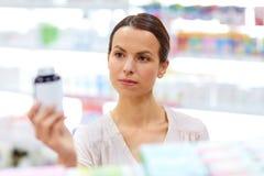Kvinnlig kund som väljer droger på apotek arkivfoto