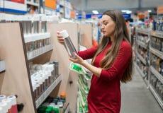 Kvinnlig kundköpandesprutmålningsfärg kan i supermarket Royaltyfri Foto
